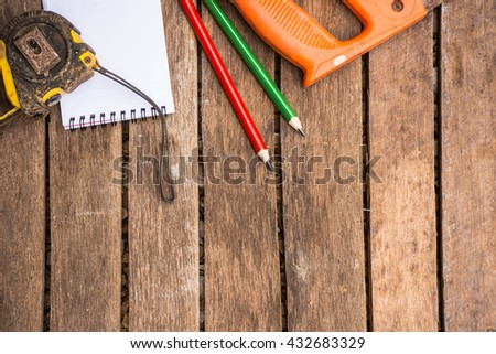 Background Craftsman tool have saw and tape measure and wood pencil  and notebook.On wooden background.Screen for carpenter. - stock photo