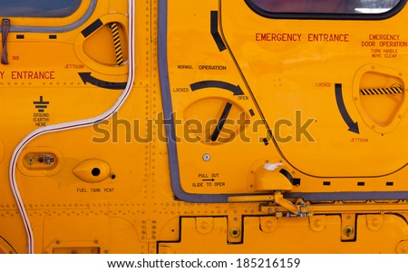 Background detail abstract of emergency handles, entrance hatches and exits on a yellow helicopter exterior - stock photo