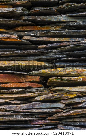 Background detail of rural house with piled schist stone blades - stock photo