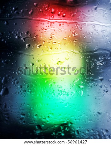 Background. Drops of a rain in the light of a traffic light. - stock photo