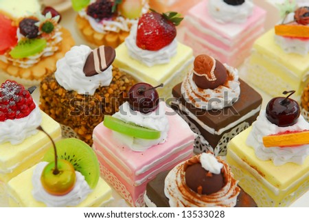 Background filled with colorful cakes and desserts with fresh fruits - stock photo
