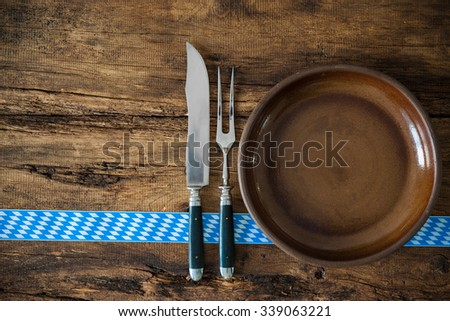 Background for Bavarian cuisine with a blue checkered ribbon and kitchen utensils - stock photo