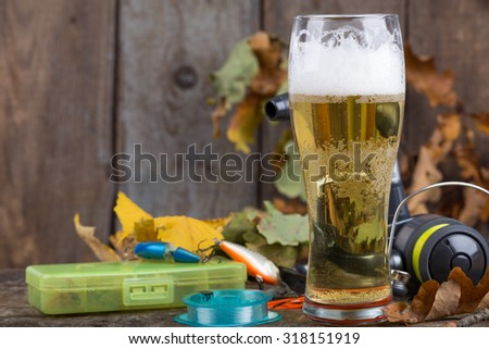 background for oktoberfest with fishing tackles and glass a beer on old wooden board with oak leaf