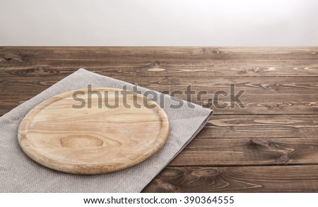 Background for product montage. Empty round wooden board with tablecloth. - stock photo