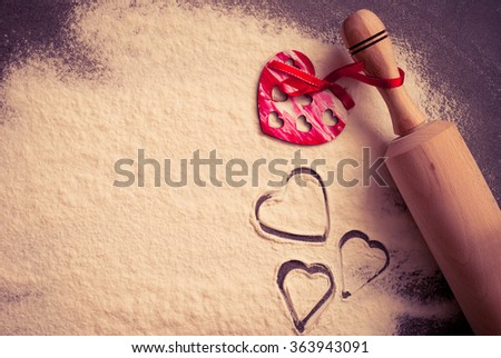 Background for Valentine's Day baking with hearts and flour.