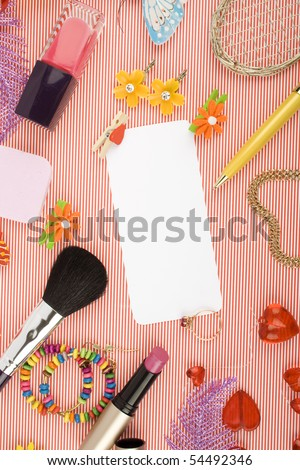 Background for Women's Day in pink. Lipstick, earrings, ring, red heart, nail polish, flowers, perfume, sparkles, white sheet of paper and pen gold