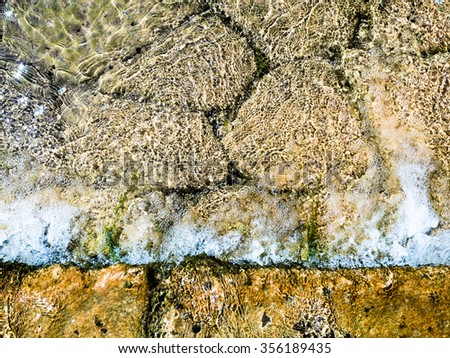 Background formed by the water of a stream flowing over rocks. - stock photo