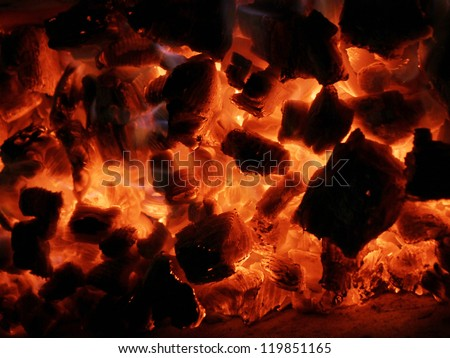 Background from a fire, firewoods and decaying red coals - stock photo