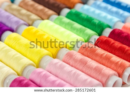 Background from bobbins with multicolored thread for sewing - stock photo