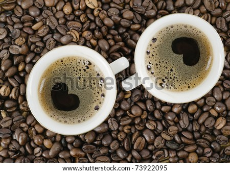 Background from coffee grains and a cup from coffee, the top vie - stock photo