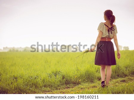Background girl walking in a field in a dress and hold dandelions in her hand in full growth - stock photo