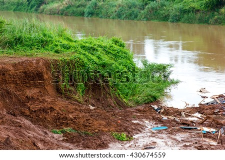 Background ground riverbank collapsed, but the remaining debris of a house was damaged. - stock photo