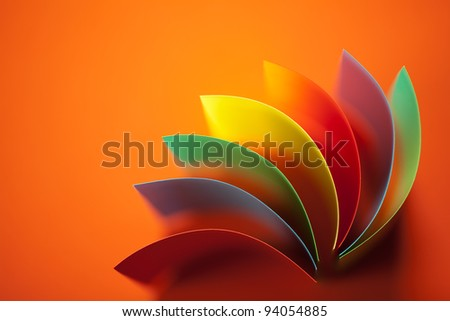 background image of colorful origami fan pattern made of curved sheets of paper, on orange background - stock photo