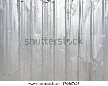 background image of distorted galvanized fence of construction site in sunlight