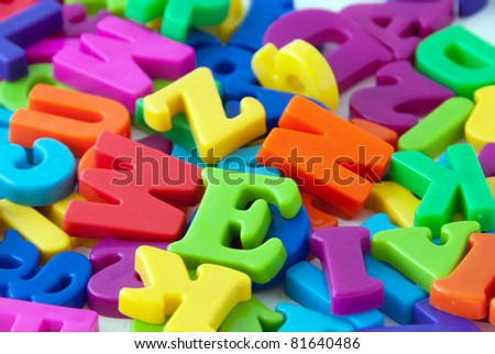 Background image of magnetic alphabet letters.