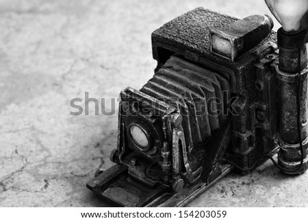 Background image of miniature vintage accordion style camera (model made from resin) on marbled tile. Macro image in black and white with shallow dof and copy space - stock photo