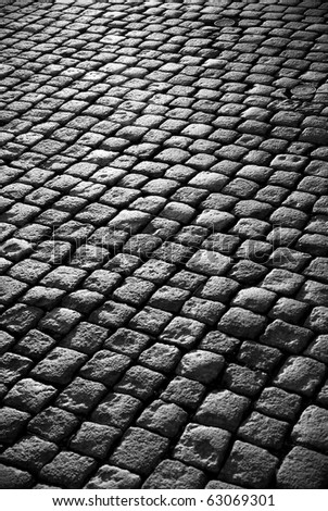 Background image of old cobblestone road backlit with low sunlight - stock photo