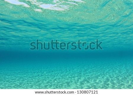 Background image of sunlight on ocean floor in clear blue water - stock photo
