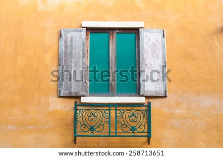 Background image of wooden window on saturate yellow wall house. - stock photo
