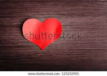 background in the style of Valentine's Day. red heart on a wooden background - stock photo