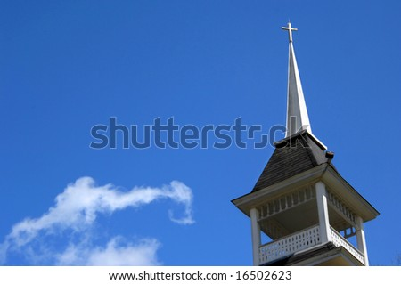 Background is filled with bright blue skies.  Church steeple in traditional wood with cross topper. - stock photo