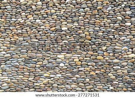 background made of a closeup of a wall with pebbles - stock photo
