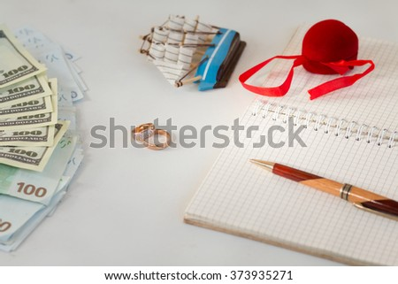 background, money , wedding rings , notebook notes pen, prepare for the wedding, plan a wedding , honeymoon - stock photo