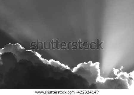 Background monochrome black and white photograph of dramatic moody cumulus clouds with sunbeams - stock photo