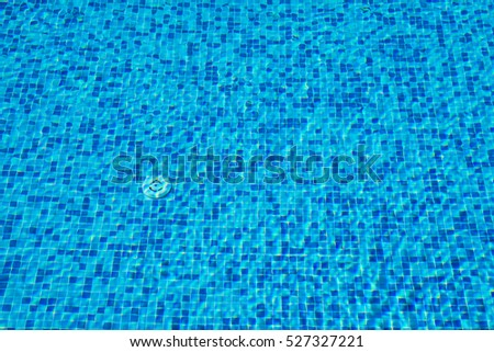 Background of a blue tiled pool with clear cool rippling water(selective focus)