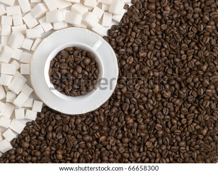 background of a cup of coffee beans with lumps of sugar - stock photo