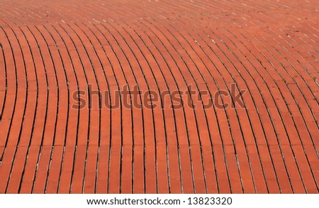 background of a curve red orange brick wall - stock photo