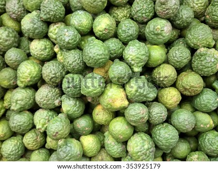 background of a pile heap of organic fresh ripe kaffir lime on displayed in a typical morning vegetable market departmental store sack - stock photo