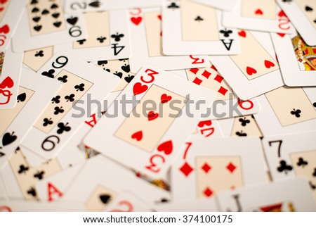 Background of a random spread of playing cards covering the surface of a table viewed full frame low angle with focus to the three of hearts and shallow depth of field - stock photo