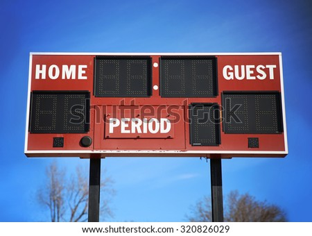background of a scoreboard with home and guests written on it in front of a blue sky on a sunny summer day  - stock photo