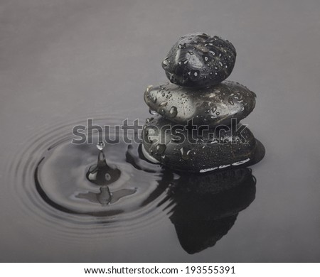 Background of a spa with black stones and dark water. Tinted image. - stock photo
