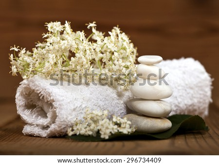 Background of a spa with white stones on a green leaf, rolled towel and flowers on wooden background. - stock photo