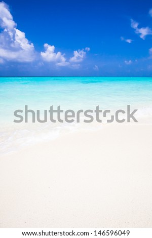 background of a white sandy beach with a turquoise sea under a deep blue sky with some white clouds - stock photo