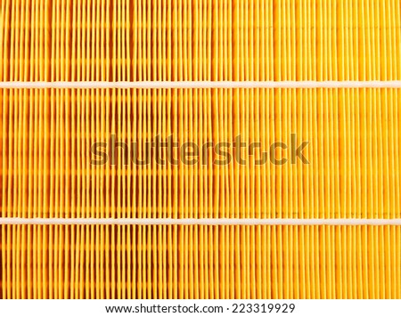Background of a yellow car air filter closeup. - stock photo