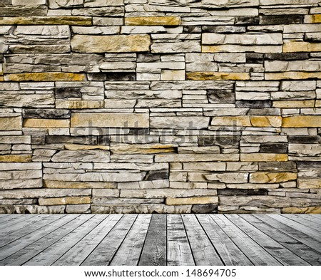 Background of aged grungy textured black brick and stone wall with light wooden floor with blackboard inside old neglected and deserted empty interior, blank horizontal space of clean studio room - stock photo