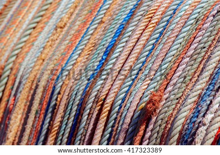 Background of aligned colorful old fishing ropes under sunlight - stock photo