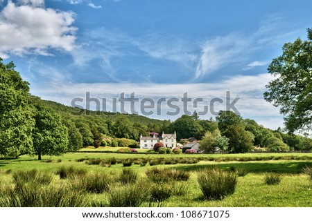 Background of an English country house nestling in lush green countryside under a blue summer sky - stock photo