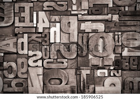 Background of antique wooden and metal letterpress printing blocks, vintage processing, sepia toned - stock photo