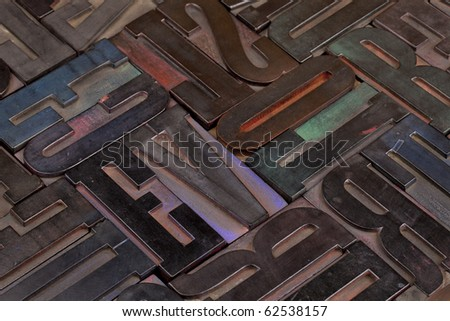 background of antique wooden letterpress printing blocks stained by color inks - stock photo
