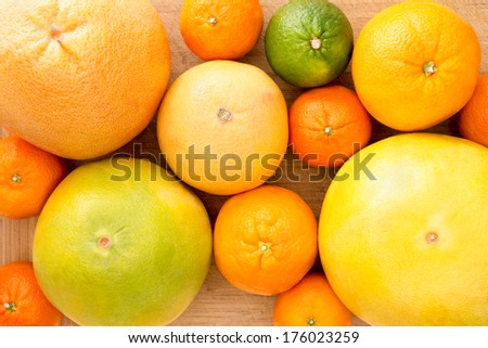 Background of assorted citrus fruit with lemon, lime, orange, tangerine, clementine and grapefruit, close up view from above on a wooden background - stock photo