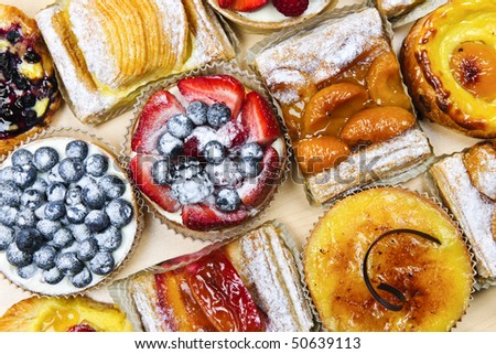 Background of assorted fresh sweet tarts and pastries from above - stock photo