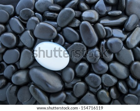 background of black stones with white stone - stock photo