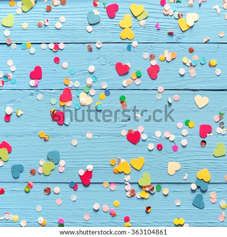 Background of blue painted wooden wall with colorful pink, red, yellow and green heart and circle confetti - stock photo