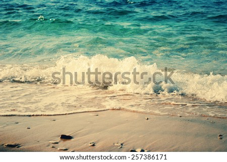 background of blurred beach and sea waves with bokeh lights, sandy beach with turquoise water, bright white sun lights bokeh, travel and summer holidays concept, vintage and retro effect - stock photo