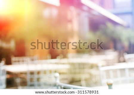 Background of blurred cafe on street of city. Tables and chairs outside in natural bokeh - stock photo