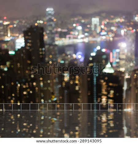 Background of blurred skyscrapers at night with reflection on the roof of building in Hong Kong, shallow depth of focus. - stock photo